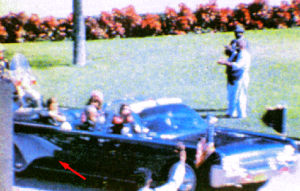 Frame 228 of the Zapruder film. Arrow points to opened umbrella.
