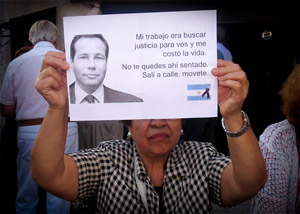 A woman hold up a picture of Alberto Nisman at a rally.
