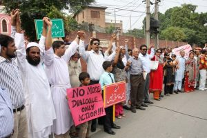 Pakistanis, mostly Muslims, form protective shield around church