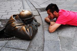 "Eye to eye with Cumil ""The Watcher,"" a bronze statue at the corner of Panska and Rybarska Brana streets in Bratislava, Slovakia. Photo Credit: seralowen / Flickr (CC BY 2.0)"