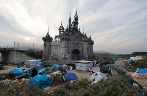 Photo by Banksy: Dismaland's dilapidated castle surrounded by tents. New shelters to come
