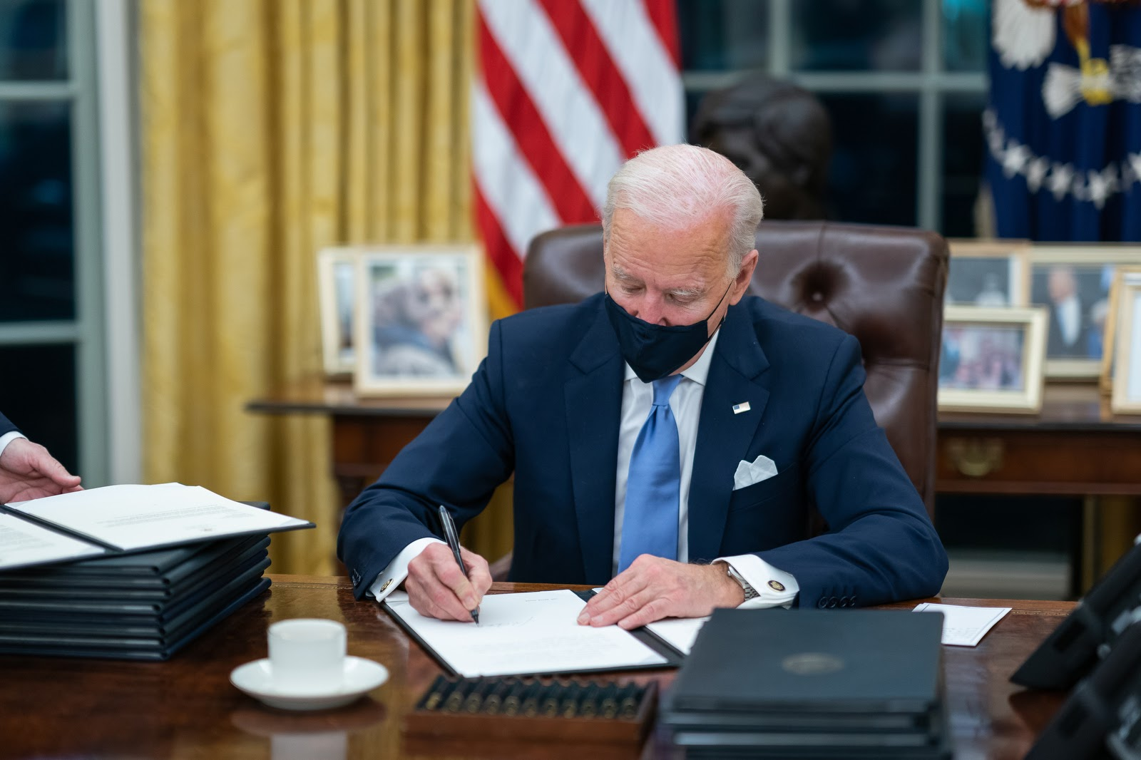 President Joe Biden signs an executive order on Jan 20, 2021.